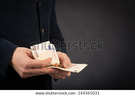 Man counting euros banknotes against black background. - stock photo