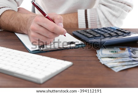 Man counting money and making notes at the table - stock photo