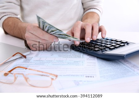Man counting money with calculator at the table - stock photo