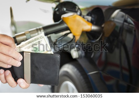 man counting money with gasoline refueling car at fuel station - stock photo