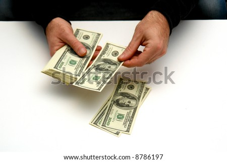 man counting out hundred dollar bills onto a white surface