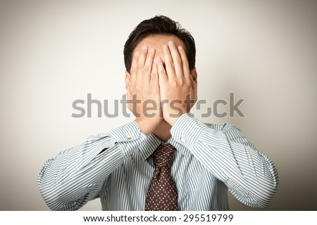 man covered his face with hand - stock photo