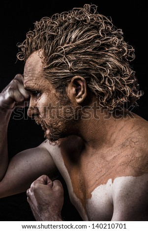 man covered in mud and naked - stock photo