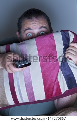 man covering face with a cushion watching tv