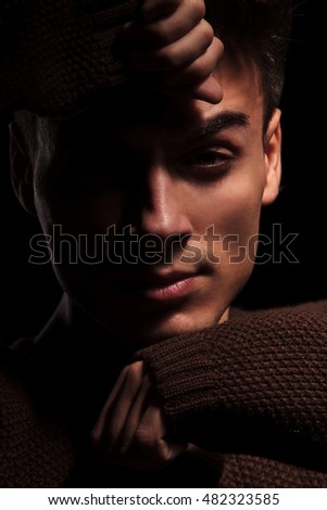 man covering face with hands on black background, closeup portrait