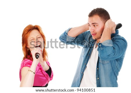 man covering his ears because girlfriend sings too loud - stock photo