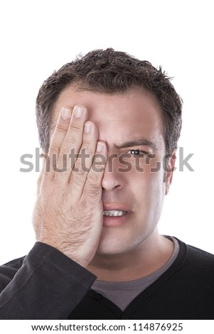 man covering his eye with his hand - stock photo