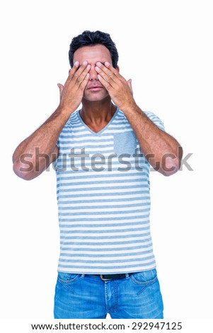 Man covering his eyes on white background