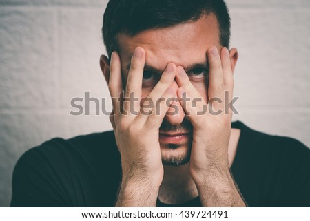 Man covering his face