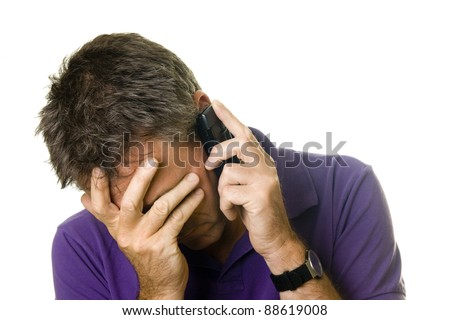 Man covering his face in distress while on the phone - stock photo