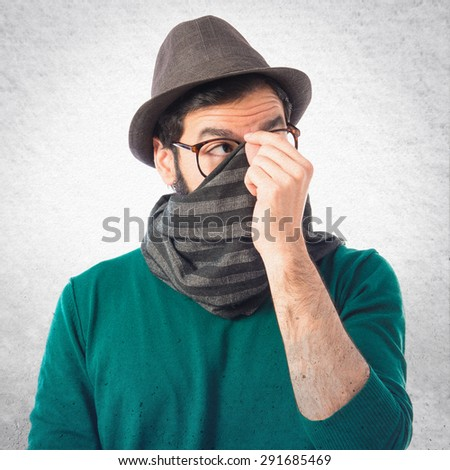 Man covering his face over grey background