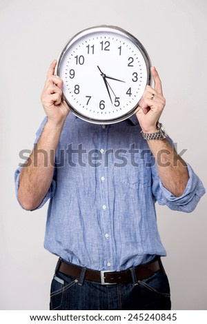 Man covering his face with analog clock
