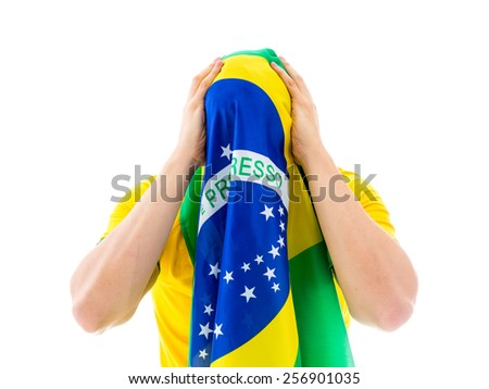 Man covering his face with the Brazilian flag - stock photo
