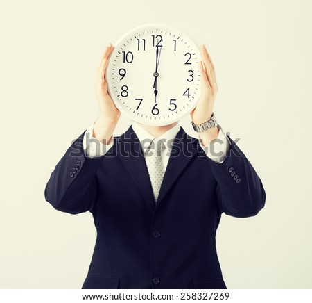 man covering his face with wall clock - stock photo
