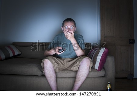 man covering mouth watching tv - stock photo