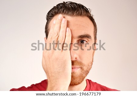 man covering one eye with hand - stock photo