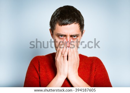 man covers  face with hands, isolated on a gray background