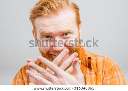 man covers his mouth with his hands and holding back laughter