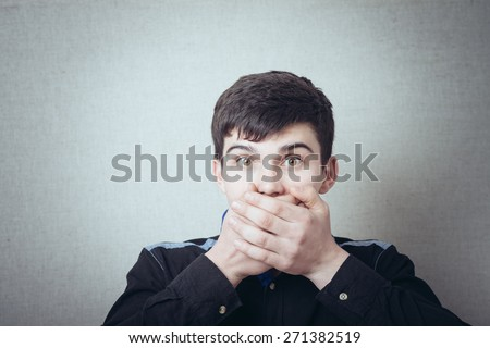Man covers his mouth with his hands not to say - stock photo