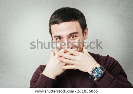 man covers his mouth with his hands so as not to laugh
