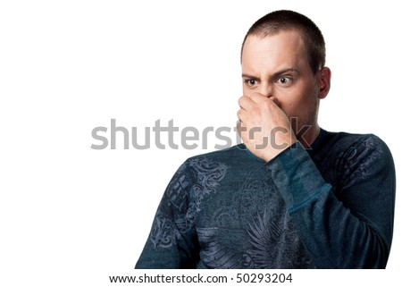 Man covers his nose, bad smells. Isolated studio shot - stock photo