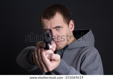 man criminal aiming with gun over grey background - stock photo