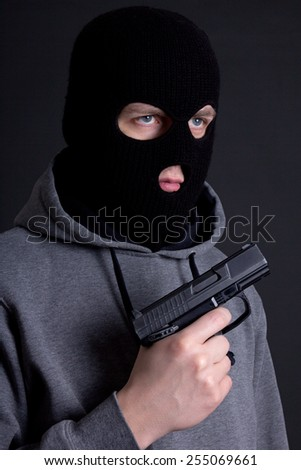 man criminal in black mask with gun over grey background - stock photo