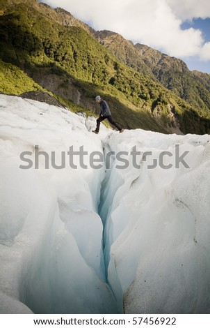 Man crosses a deep crevasse on a glacier, New Zealand