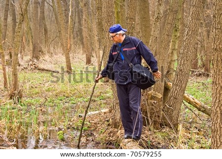 man crossing a swamp - stock photo