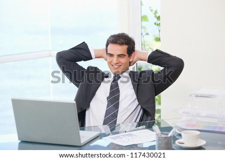 Man crossing his arms behind his head  in an office - stock photo
