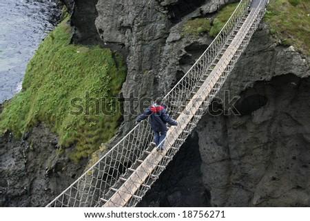 man crossing rope bridge in Ireland - stock photo