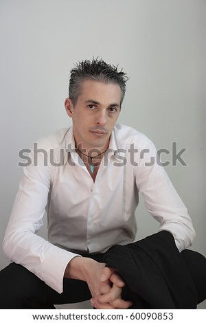 man crouched on his legs - stock photo