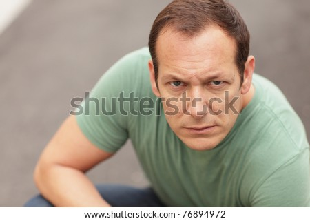 Man crouching and making a mean facial expression - stock photo