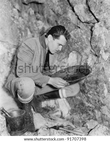 Man crouching and panning for gold - stock photo