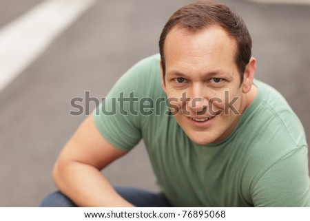 Man crouching and smiling - stock photo