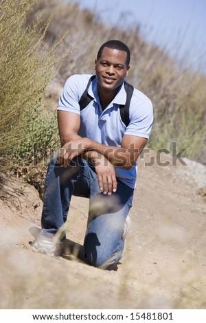 Man crouching on path to beach smiling - stock photo