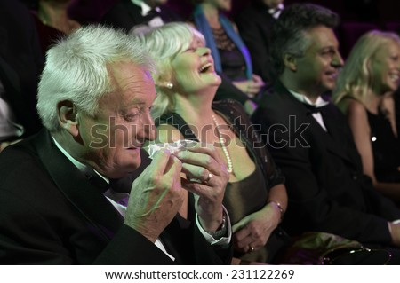 Man Crying at the Theater With Others Laughing - stock photo