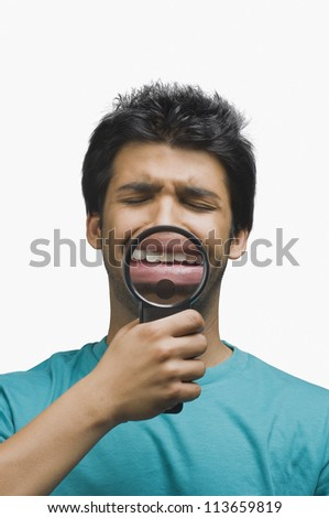 Man crying in front of a magnifying glass - stock photo