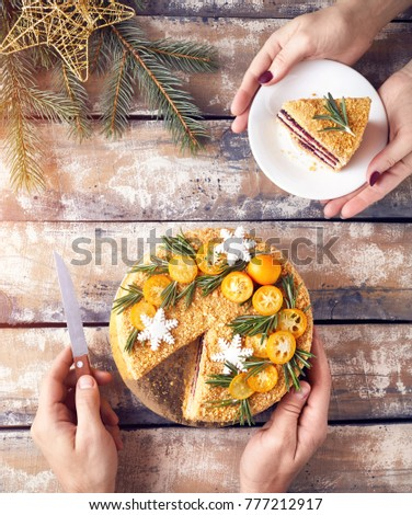 Man cut Christmas Honey cake and woman holding piece on the plate at breakfast.