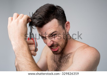 man cut hair with scissors with mad eyes. Bad day at the hairdresser.Studio shot. Gray background - stock photo