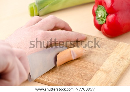 man cut in his finger with a knife - stock photo