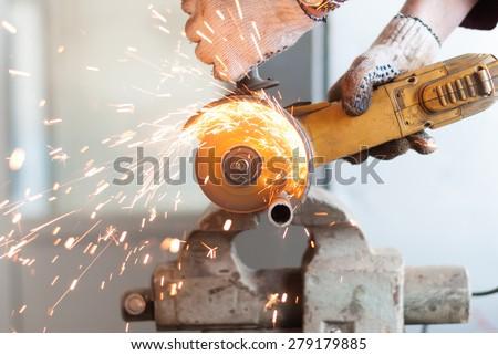Man cuts a metal pipe. - stock photo