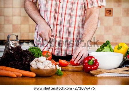 Man cuts fresh spring vegetables on the kitchen table, closeup. Preparing homemade food, home kitchen interior.