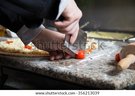 Man cuts fresh tomatoes by very sharp knife at the kitchen worktop. He is going to add this to vegetarian pizza.  - stock photo
