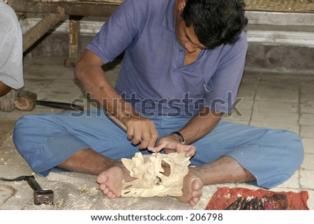 Man cutting a wooden mask - stock photo