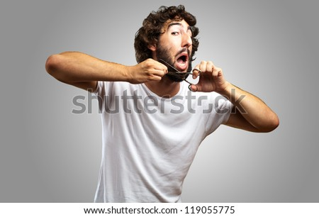 Man Cutting Beard against a grey background - stock photo