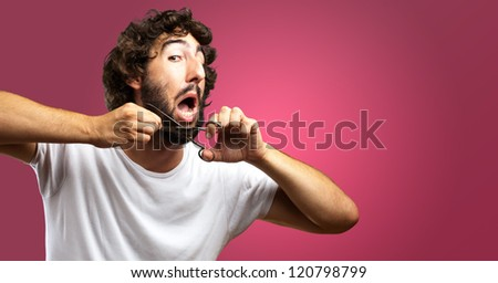 Man Cutting Beard against a pink background