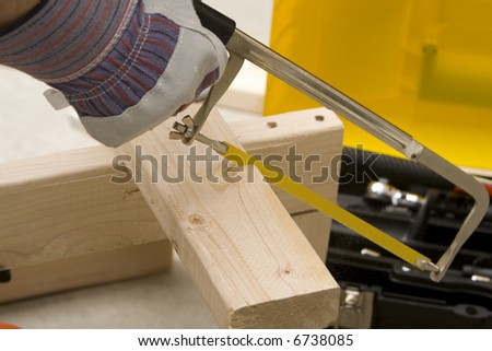 man cutting board with a saw - stock photo
