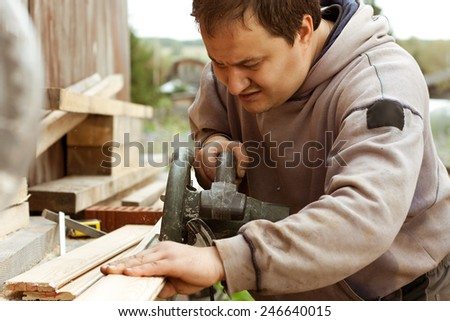 Man cutting boards of wood to size using circular saw - stock photo