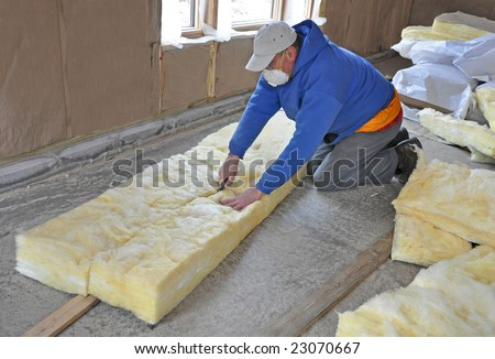Man cutting fiberglass insulation - stock photo